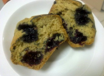 mulberry muffin cut in half on a plate